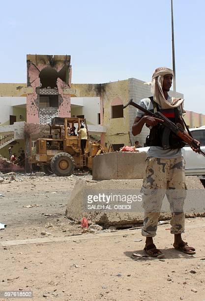 A member of Yemeni security forces stands guard at the site of a suicide car bombing claimed by the Islamic State group on August 29 2016 at an army...