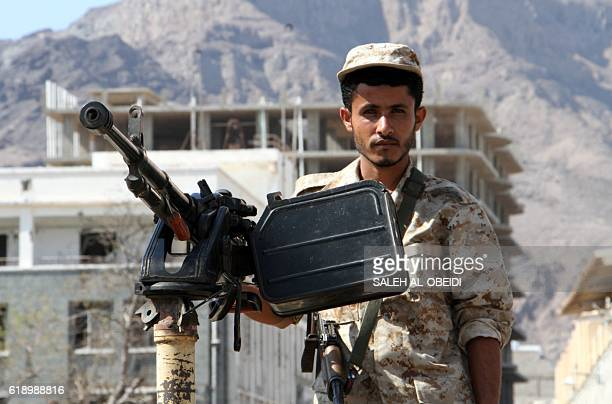 A member of Yemeni security forces stands guard at the site where a suicide car bomb exploded next to the central bank in Yemen's second city Aden on...