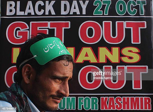 A member of Youth Forum for Kashmir is seen in front of a placard during the protest against Indian presence in the Himalayan region in Lahore...