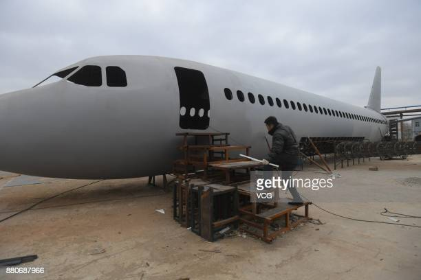 A member of Zhu Yue's team works on the homemade Airbus A320 jet plane at an open space in Tieling Liaoning Province of China Motorcycle mechanic Zhu...