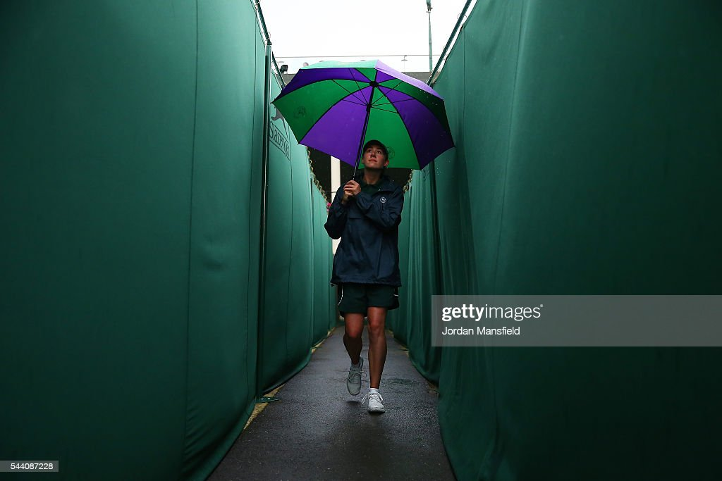 A member off staff walks on during day five of the Wimbledon Lawn Tennis Championships at the All England Lawn Tennis and Croquet Club on July 1, 2016 in London, England.