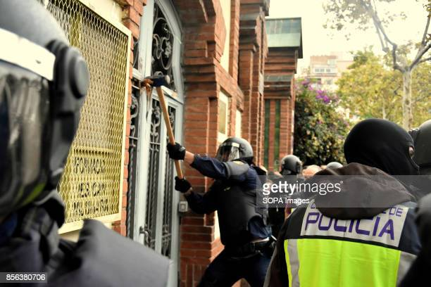 A member os the spanish police is seen destroying a door with a hammer National Police entered by force in the High School of L´Hospitalet City where...