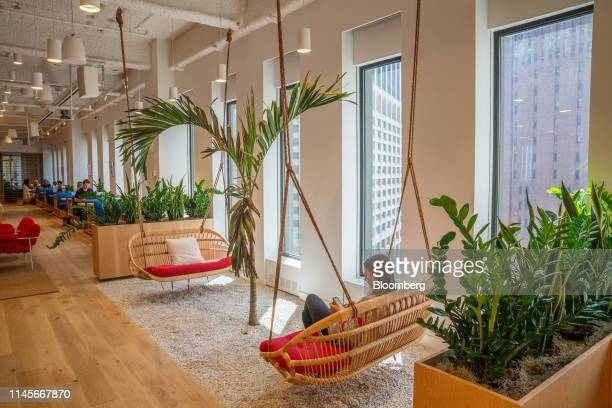 Member sits in a lounge area at the WeWork Cos Inc. 85 Broad Street offices in the Manhattan borough of New York, U.S., on Wednesday, May 22, 2019....