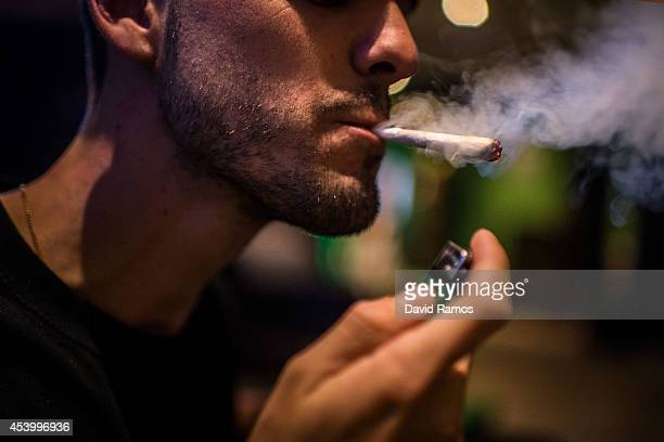 A member smokes a marijuana joint in a cannabis club on August 22 2014 in Barcelona Spain Under Spanish law marijuana can be consumed and grown for...