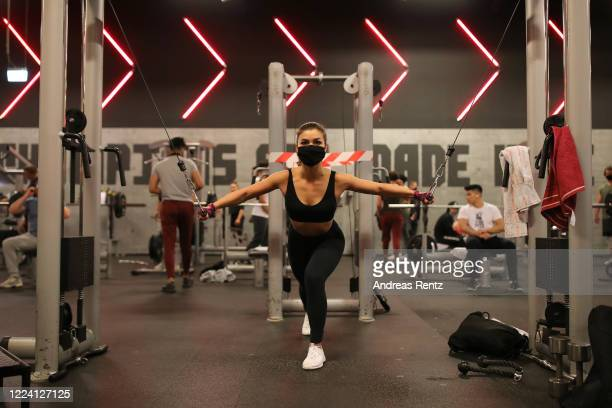 Member wears a protective face mask and exercises on a fitness machine during his fitness training at a McFit training studio branch after midnight...