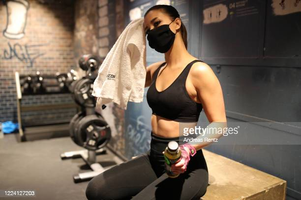 Member wears a protective face mask and exercises on a fitness room during her fitness training at a McFit training studio branch after midnight...