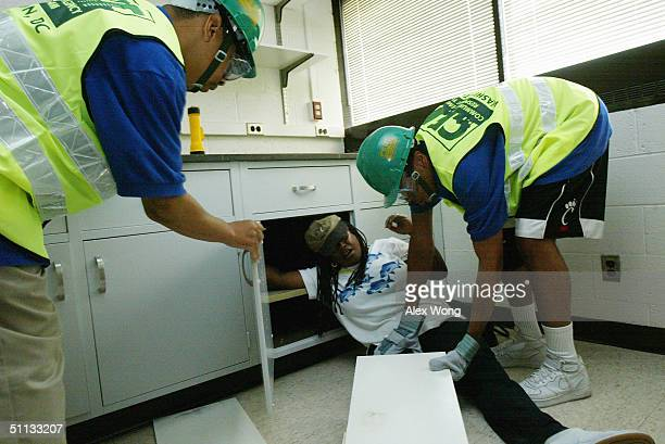Members Aaron Lindsay and Juan Quick of Team DC help an unidentified victim during a drill test of a simulated disaster situation as part of the...