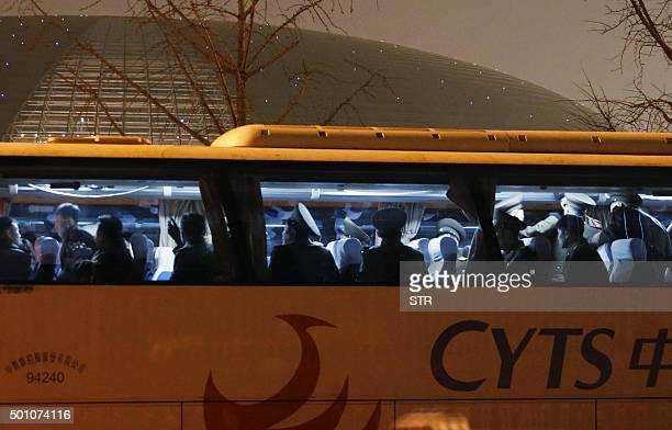 Members and officials of North Korea's State Merited Chorus leave China's National Center of Performance Arts in Beijing on December 12 before...