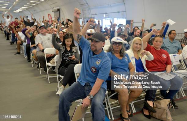 ILWU members and supporters express their objections with thumbs down during another Harbor Commission meeting to vote on the appeal regarding the...