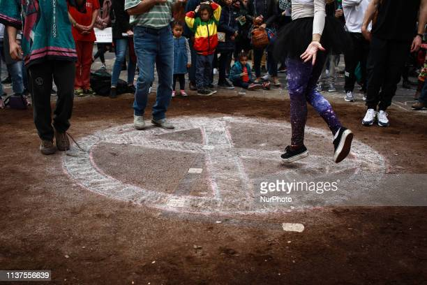 Members and supporters of climate change activist group Extinction Rebellion dance on soil spread on the road at Oxford Circus in London England on...