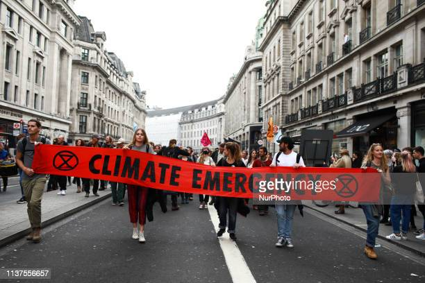 Members and supporters of climate change activist group Extinction Rebellion march along Regent Street in London England on April 16 2019...