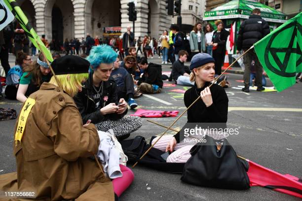 Members and supporters of climate change activist group Extinction Rebellion block Piccadilly Circus in London England on April 16 2019...