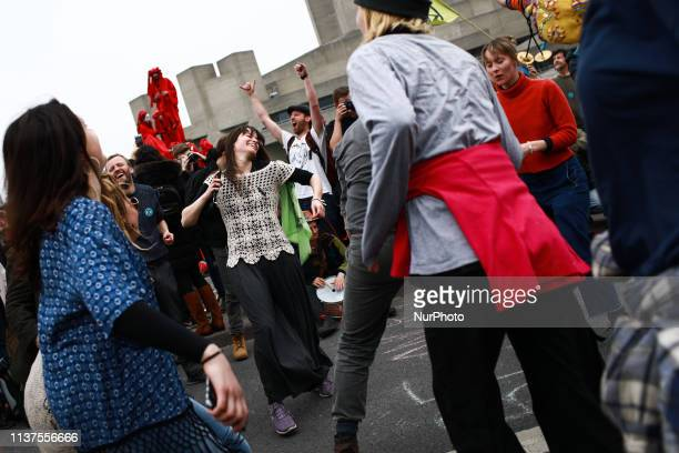 Members and supporters of climate change activist group Extinction Rebellion dance on Waterloo Bridge in London England on April 16 2019...