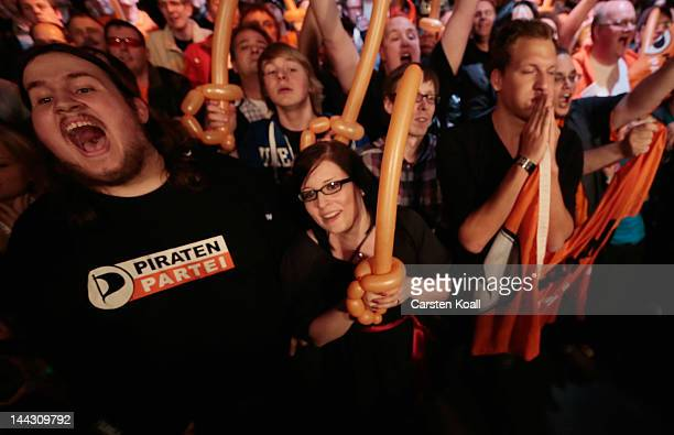 Members and supporters of Germany's Pirate Party react to the announcement of initial exit poll results that give the Pirates 76 % of the vote enough...