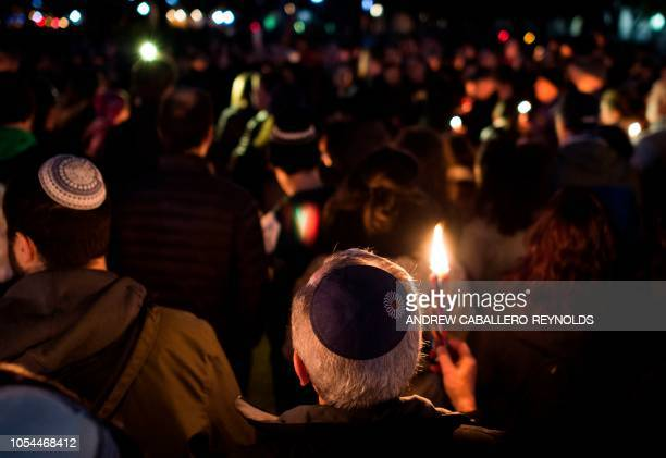 TOPSHOT Members and supporters of the Jewish community come together for a candlelight vigil in remembrance of those who died earlier in the day...