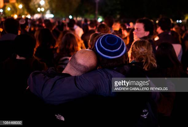Members and supporters of the Jewish community hug as they come together for a candlelight vigil in remembrance of those who died earlier in the day...