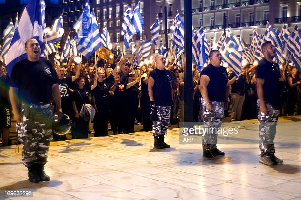 Members and supporters of the ultranationalist Golden Dawn party chant the national anthem in front of the Greek parliament in central Athens on May...