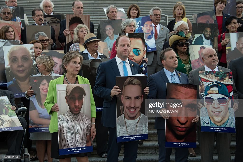 Members and supporters of the US Congressional LGBT Equality Caucus hold pictures of victims of the Pulse nightclub attack, one month after a gunman killed 49 people at the club in Orlando, Florida, during a vigil on the East House steps of the US Capitol in Washington, DC, on July 12, 2016. / AFP / NICHOLAS