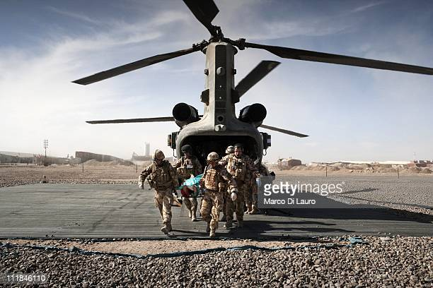 MERT members carry a stretcher with a wounded British soldier out of the MERT CH47 Chinook helicopter as they land to the Camp Bastion Hospital on...
