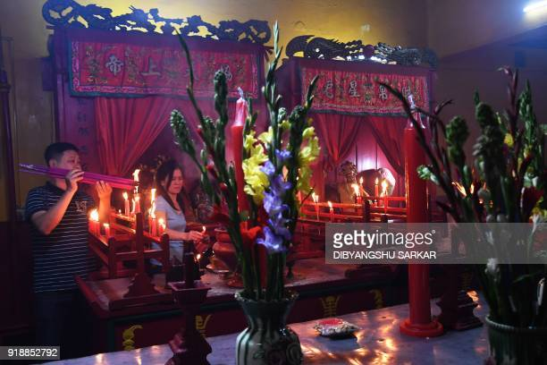 Members Chinese community pray a the community temple as they welcome the Lunar New Year of the dog at the China town area in Kolkata on February 16...
