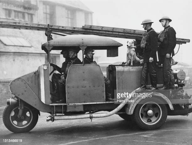 Members for the Auxiliary Fire Service in West Croydon travel aboard their three wheeled fire engine based on the Scammell Mechanical Horse with...