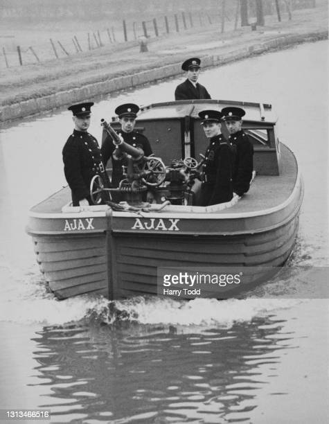 Members for the Auxiliary Fire Service of the Enfield Fire Brigade undergo training with a traversable powered fire hose pump aboard a converted...