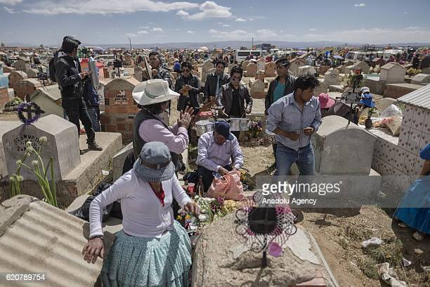 Members from a family dance while a band musicians dedicate a song to a deceased during the Day of the Dead festivity at Mercedario cemetery in the...