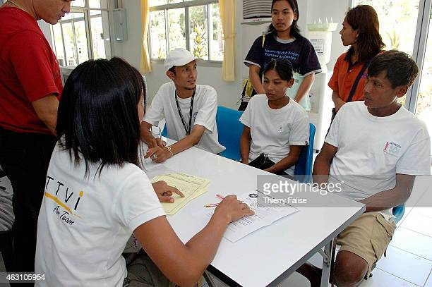 Members from IOM's Migrant Health Project accompany two Burmese migrants at the Thai Tsunami Victim Identification office in Bang Maruan temple The...