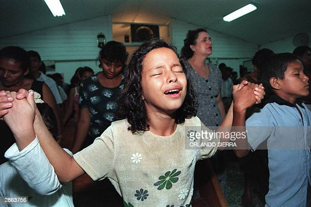 Members from the evangelical church pray and sign 28 July 1998 in Evenezzer church in San Pedro Sula 240 kilometers north of Tegucigalpa The church...