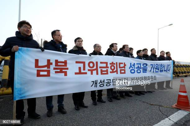 Members from the Gaeseong Industrial Complex association hold a banner wishing successful talks between South Korea and North Korea at a military...