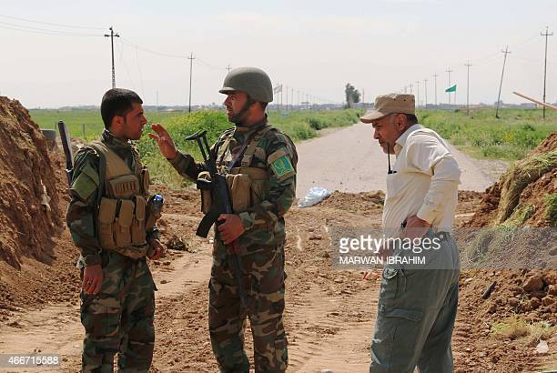 Members from the Iraqi fighters of the Popular Mobilisation units and Shiite Turkmen combatants talk as they plan to head towards the city of...