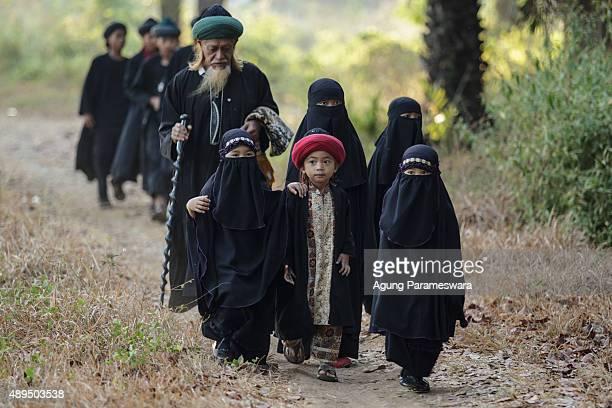 Members from the Islamic commune AnNadzir walk through oil palm plantation to attend Eid Al Adha mass prayer at Mawang Lake Gowa Regency on September...