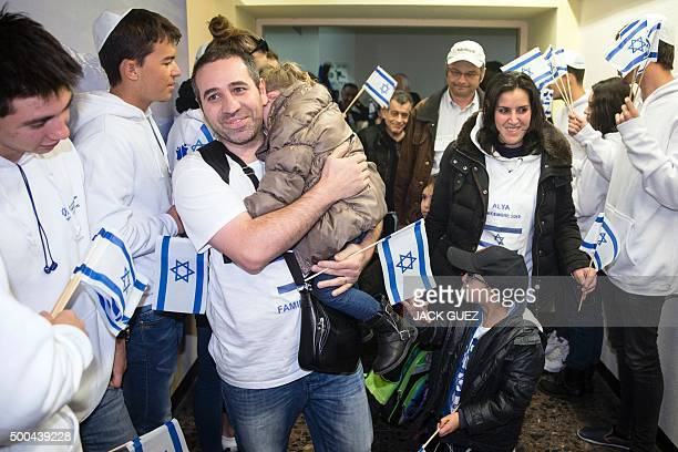 Members from the Jewish new immigrants family of Ammar from France who are making Aliyah are welcomed by Israelis waving national flags upon their...