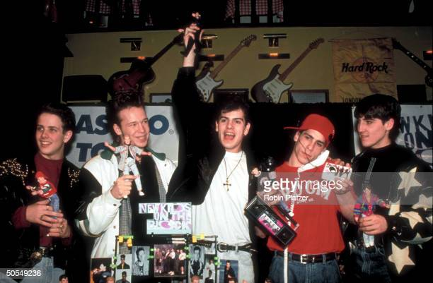 Members from the rock group New Kids on the Block holding up NKOTB merchandise