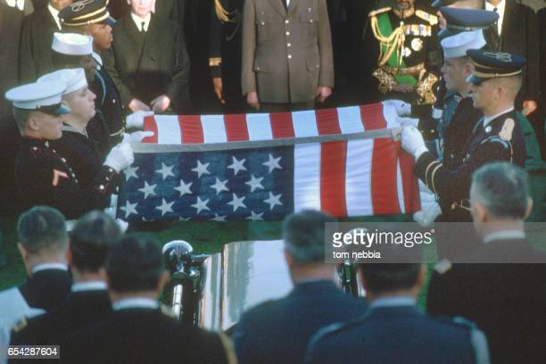 Members from the various US military services fold an American flag at President John F Kennedy's gravesite during his funeral at Arlington National...