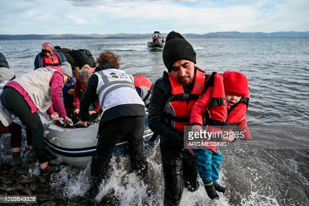 TOPSHOT NGO members help 15 Afghan refugees 5 children 3 women and 7 men to disembark from a dinghy as it lands ashore the Greek island of Lesbos on...