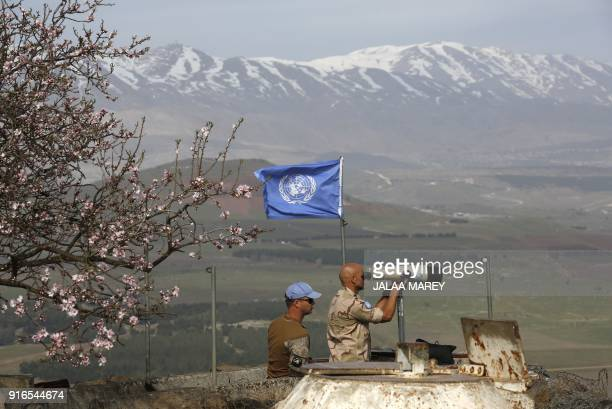 TOPSHOT UN members look through binoculars as they monitor the IsraelSyria border in the Israeliannexed Golan Heights on February 10 2018 Israel...