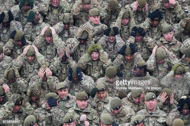 Members of 1st Battalion Welsh Guards rearrange their berets for a regimental photograph before the combined St David's Day celebration and...