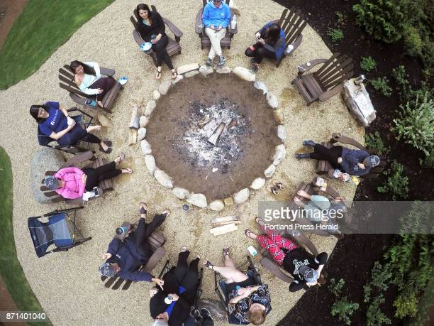 Members of a bachelorette party gather around the fire ring at breakfast after spending the night in the luxury tents at Sandy Pines Campground in...