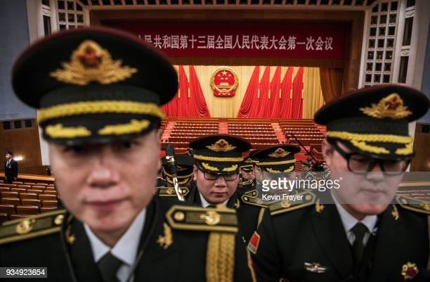Members of a band from the People's Liberation Army leave following a speech by China's President Xi Jinping after the closing session of the...
