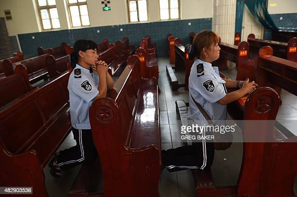 Members of a band pray inside the Sacred Heart of Jesus Catholic church after Father Joseph Zhang Yilin was ordained as a bishop in Anyang China's...