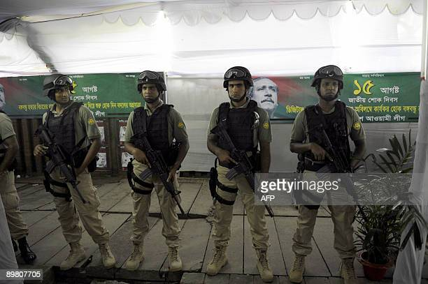 Members of a Bangladesh SWAT team stand guard in front of a banner of Sheikh Mujibur Rahman near the Sheikh Mujibur Rahman Memorial in Dhaka on...
