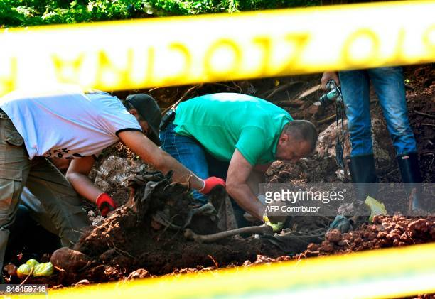 Members of a Bosnian forensic experts team and workers find human remains at the site of a newly discovered mass grave in the village of Tugovo near...