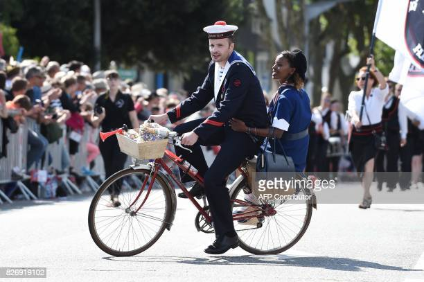 Members of a breton bagad perfom on a bike perform on August 6 2017 in Lorient western France during the traditional street parade of the 47th...