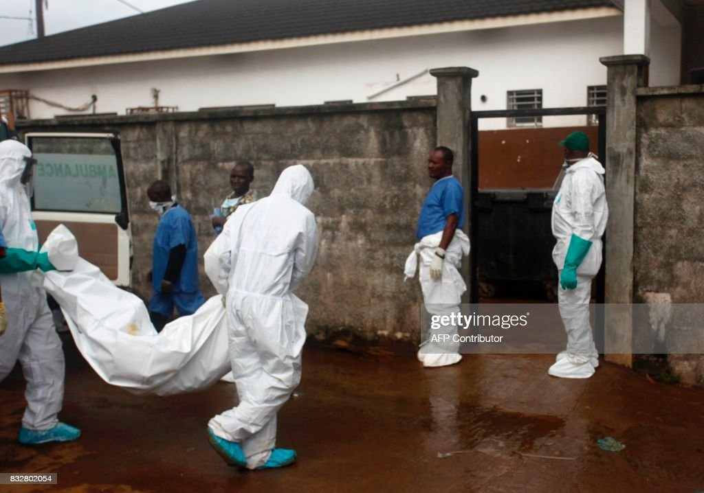 Members of a burial team carry the bodies of victims from an ambulance into a morgue in Freetown, Sierra Leone, on August 16, 2017. Sierra Leone began a weeklong period of national mourning on Wednesday as it emerged that 105 children were killed by the mudslides and torrential flooding that have left 600 people still missing in Freetown, in one of the worst natural disasters to hit the country. / AFP PHOTO / Mohamed Saidu BAH