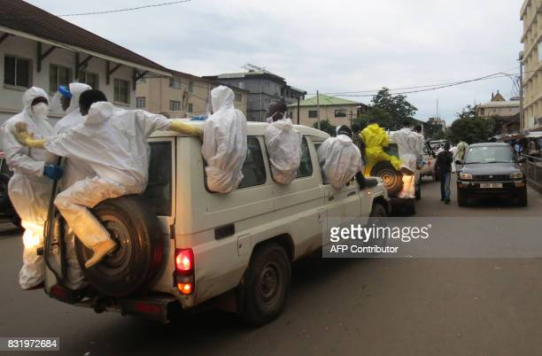 TOPSHOT Members of a burial team ride on an ambulance outside the Connaught Morgue in Freetown on August 15 2017 Sierra Leone's president issued a...