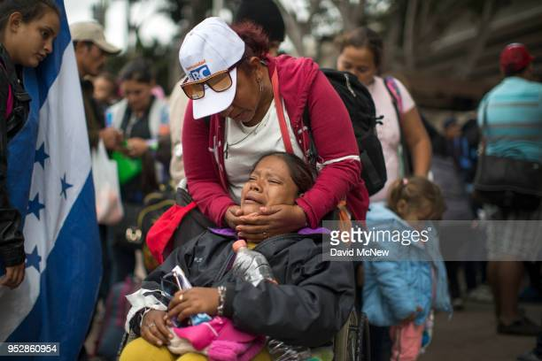 Members of a caravan of Central Americans who spent weeks traveling across Mexico walk from Mexico to the US side of the border to ask authorities...