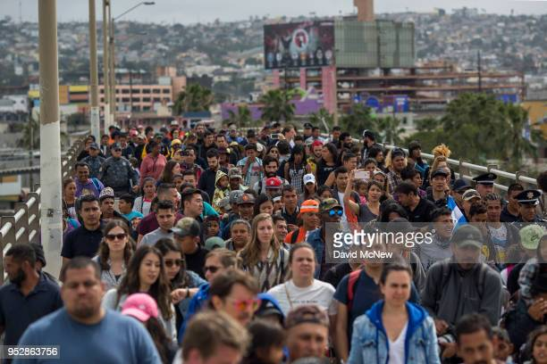 Members of a caravan of Central Americans who spent weeks traveling across Mexico walk from Mexico to the US side of the border with supporters to...