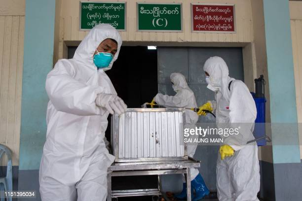 Members of a charity organisation disinfect the coffin of a person who died from the H1N1 influenza virus during a funeral service at Yay Way...