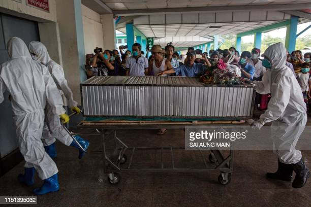 Members of a charity organisation transport the body of a person who died from the H1N1 influenza virus for a funeral service at Yay Way cemetery in...